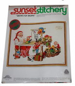 Sunset Stitchery - Santa's Toy Shoppe Design By Charlene Gerrish - Features Santa and His Elves Preparing for Christmas. Includes Alphabet to Print Names on Sant'a List. - Fits 36cm By 46cm Frame - Kit is dated 1979