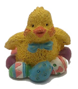 EASTER CHICK FIGURINE SITTING ON EASTER EGGS
